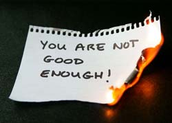 "A burning paper with ""You Are Not Good Enough"" written on it"